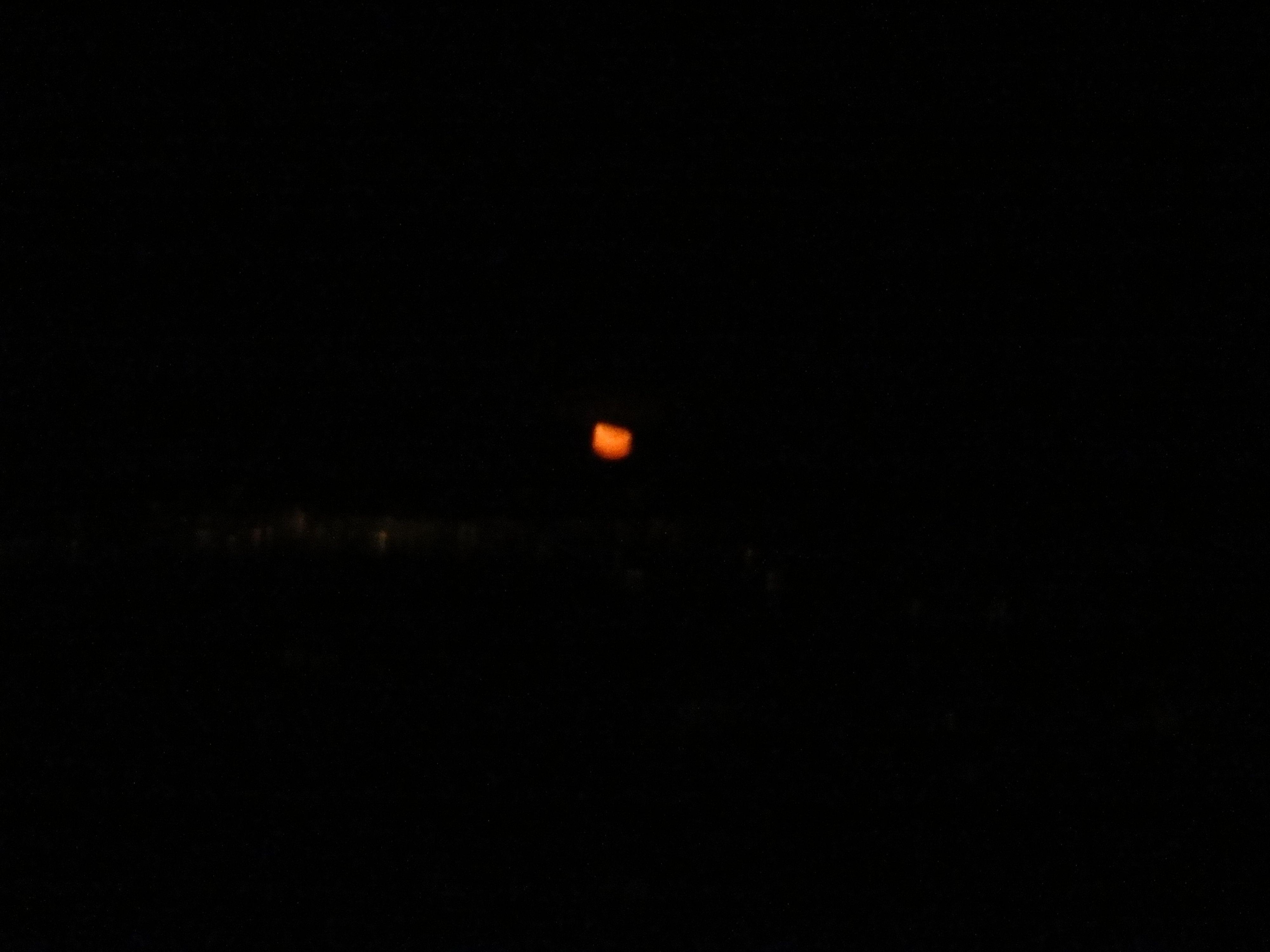 Manches sieht man unterm Weihnachtsbaum am Gabentisch nicht: Mondaufgang in knallorange über der dichten Wolkendecke.