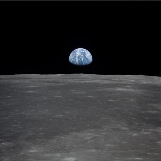 """Aussicht vom Apollo 11-Raumschiff mit Blick auf die Erde, die sich über dem Mondhorizont erhebt. Das abgebildete Mondgelände befindet sich in der Nähe von Smyth's Sea. Koordinaten der Mitte des Geländes sind 85 Grad östlicher Länge und 3 Grad nördlicher Breite. Während die Astronauten Neil A. Armstrong, Kommandant, und Edwin E. Aldrin Jr., Pilot des Mondmoduls, mit der Mondlandefähre """"Eagle"""" landen, um den Mond zu erkunden, umkreiste Astronaut Michael Collins, Pilot des Kommandomoduls, im Kommando- und Servicemodul (CSM) """"Columbia"""" den Erdtrabanten. Foto: NASA"""